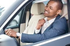 Young businessman driver sitting inside car driving holding collar aside feeling hot side view in window close-up stock photography