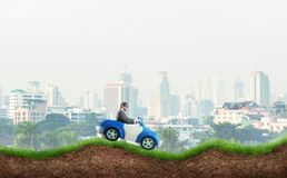 Young businessman driving a toy car Royalty Free Stock Images