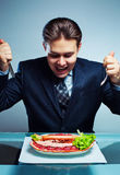 Young businessman eating Royalty Free Stock Image