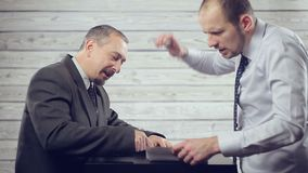 Businessmen argue among themselves. A young businessman and an elderly man argue furiously. Businessmen shout at each other and fight foreheads and shift stock video footage