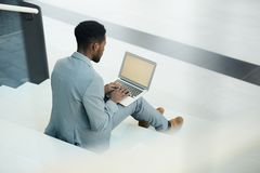 Analyst working. Young businessman in elegant grey suit sitting on staircase with laptop on knees and surfing in the net for financial data stock photos