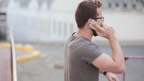 Young businessman emotionally talks by smartphone, having problems. Guy with beard and glasses uses phone on the street. stock video
