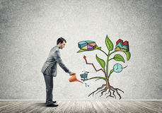 Young businessman in empty room watering drawn growth concept with can Stock Images