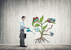 Young businessman in empty room watering drawn growth concept with can Stock Photo