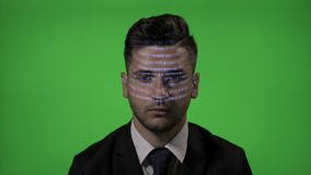 Young businessman entrepreneur working in IT industry having a hologram programming code on face on a green screen background -. Young businessman entrepreneur stock video