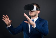 Young businessman experiencing vr reality. Thru modern headset Stock Image