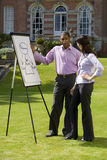 Young businessman explaining chart on whiteboard to colleague outdoors Royalty Free Stock Images
