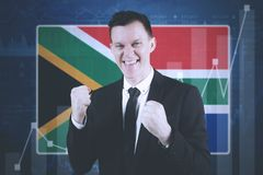 Successful businessman with South African flag. Young businessman expressing success while standing near growth statistics and South African flag stock images