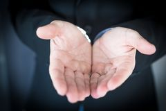 Young businessman extending hands asking for help. A young businessman asking for help royalty free stock photo