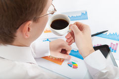 Young businessman in eyeglasses dinking coffee Stock Photography