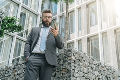 Young businessman in eyeglasses, suit and tie is standing outdoor,using smartphone computer. In background is modern glass building. Man working. Business Stock Image