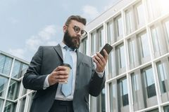 Young businessman in eyeglasses, suit and tie is standing outdoor, using smartphone computer and drinking coffee. Royalty Free Stock Photo