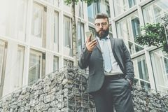 Young businessman in eyeglasses, suit and tie is standing outdoor,using smartphone computer. In background is modern glass building. Man working. Business Stock Images