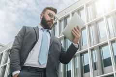 Young businessman in eyeglasses, suit and tie is standing outdoor,using tablet computer. Stock Photos