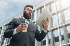 Young businessman in eyeglasses, suit and tie is standing outdoor, using tablet computer and drinking coffee. In background is modern glass building. Man Stock Photo