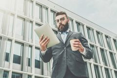 Young businessman in eyeglasses, suit and tie is standing outdoor, using tablet computer and drinking coffee. In background is modern glass building. Man Stock Photography