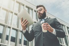 Young businessman in eyeglasses, suit and tie is standing outdoor, using tablet computer and drinking coffee. In background is modern glass building. Man Royalty Free Stock Images