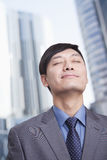 Young businessman with eyes closed and head back smiling, portrait, skyscrapers in the background Royalty Free Stock Photography