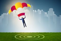 The young businessman falling on parachute in business concept Royalty Free Stock Images