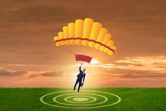 The young businessman falling on parachute in business concept Stock Image