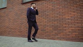 Young businessman feeling annoyed while talking on the cell phone outdoors near modern brick wall. Man angry and sad. Young businessman feeling annoyed while stock video