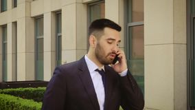 Young businessman feeling annoyed while talking on the cell phone outdoors near office building center. Man angry and. Sad stock footage