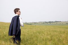 Young businessman in field. Aspiring businessman standing in a field thinking about starting a business Stock Photo