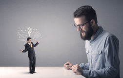 Young businessman fighting with miniature businessman Stock Images