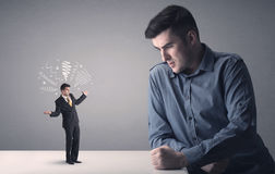 Young businessman fighting with miniature businessman Royalty Free Stock Photo