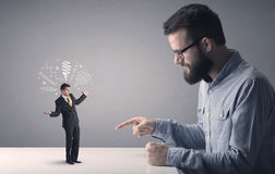 Young businessman fighting with miniature businessman Royalty Free Stock Images