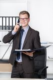 Young businessman with file is phoning in the office Stock Photography