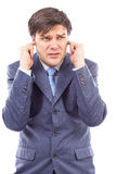 Young businessman with fingers in his ears  protecting himself f Stock Images