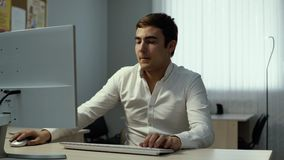 Young businessman finishes working on desktop in office and gets up from desk stock video