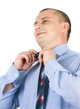 Young businessman fixing his tie isolated on white Royalty Free Stock Image