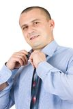 Young businessman fixing his tie isolated on white Royalty Free Stock Images
