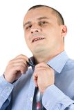 Young businessman fixing his tie isolated on white Stock Photo