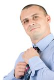 Young businessman fixing his tie isolated on white Stock Photography
