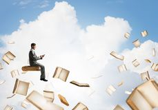 Man using smartphone and many books flying in air. Young businessman floating in blue sky with smartphone in hands Royalty Free Stock Photo
