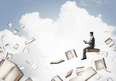 Man using smartphone and many books flying in air. Young businessman floating in blue sky with smartphone in hands Stock Images