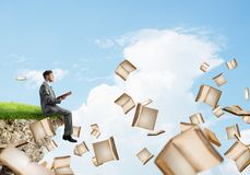 Man reading book and many of them flying in air. Young businessman floating on edge of a cliff with red book in hands Stock Photography