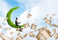 Man using smartphone and many books flying in air. Young businessman floating on green moon in blue sky with smartphone in hands Royalty Free Stock Photo
