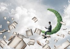 Man using smartphone and many books flying in air. Young businessman floating on green moon in blue sky with smartphone in hands Royalty Free Stock Images