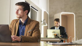 Young Businessman Focused on Work. Two career people in the office. Medium shot. Shot on RED Epic stock footage