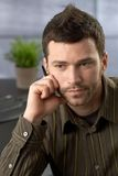 Young businessman focusing. On task in office royalty free stock image