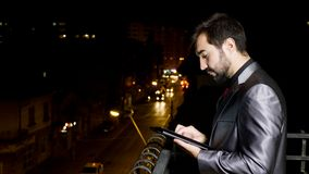 Young businessman in formal suit at the balcony using a tablet PC stock video footage