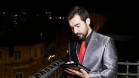 Young businessman in formal suit at the balcony using a tablet PC stock footage