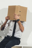 Young businessman in formal wear hiding face with folder in office Stock Photos