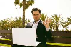 Young businessman in formalwear typing on laptop keyboard and showing symbol OK while sitting at bench outdoor. Blurred Royalty Free Stock Photo
