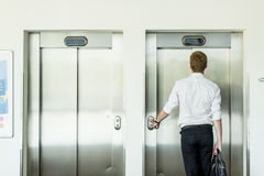 Young businessman in front of  elevator Stock Photo