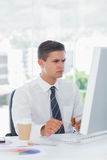 Young businessman frowning while looking at computer Royalty Free Stock Photography